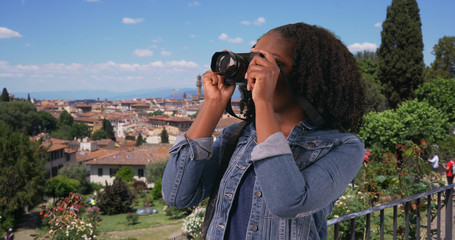 Smiling portrait of excited tourist taking photos with camera in Florence