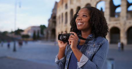 Cheerful tourist at Roman coliseum at dusk taking pictures with camera