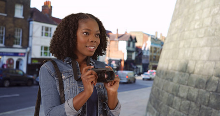 Pretty black female on urban street in England takes photo with camera smiling
