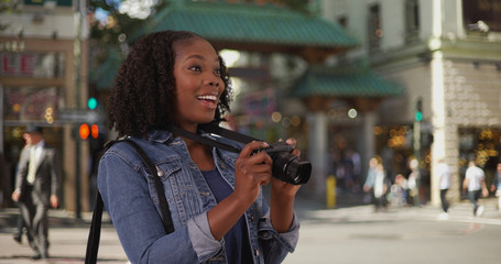 Attractive black woman takes picture near Chinatown entrance in San Francisco