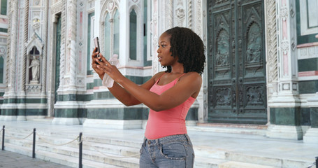 Cute black woman takes a selfie with smartphone outside cathedral in Florence