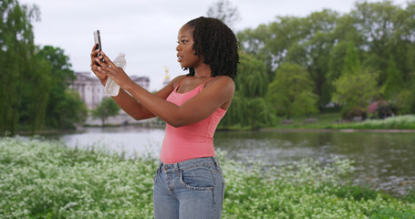 Cute African American woman takes a selfie at St. James park in London