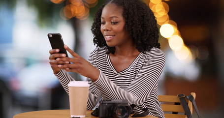 Smiling black woman sits at cafe table outdoors looking at mobile phone