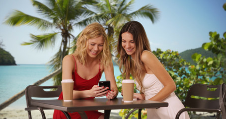 Couple of cute girls sharing smart phone in the Bahamas