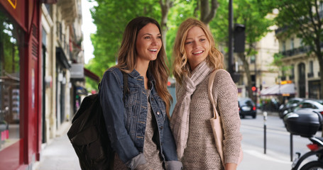 Two friendly girls standing laughing and gossiping in front of some Paris shops