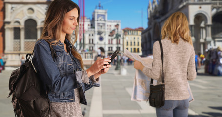 Blonde woman looking at map in Venice, Italy while friend takes selfie