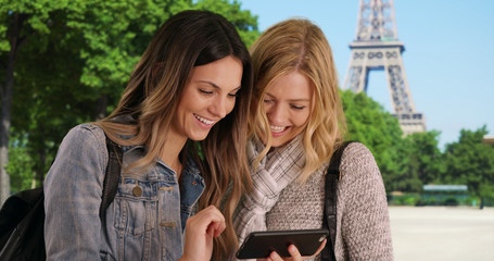 Two happy girlfriends looking at smartphone pictures in Paris near Eiffel Tower