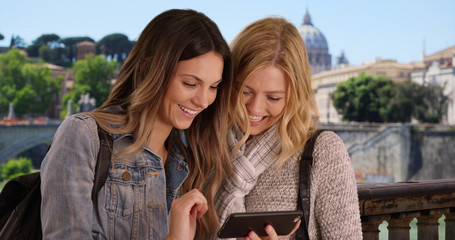 Two female tourists in Rome scrolling through their vacation photos on phone