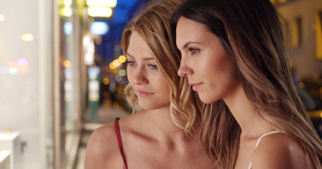 Brunette and blonde posing with seriousness together outside shop in the city