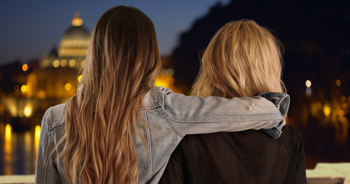 Young brunette with arm around blonde friend's shoulder in Rome, Italy