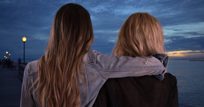 Two female friends share friendly moment together at the pier at dusk