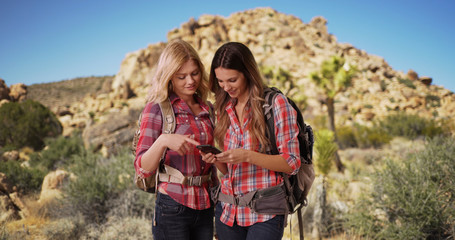 Two active Caucasian females using phone while out hiking in the desert
