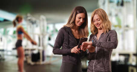 Young attractive fitness women looking at smartphone and watch at the gym