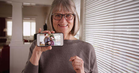 Caucasian grandmother showing video clip of family during Christmas on phone
