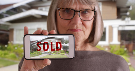 Elderly white woman holding phone with picture of home that was recently sold