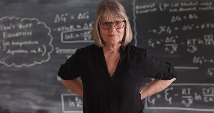 Old senior woman teacher with serious attitude posing in front of chalkboard