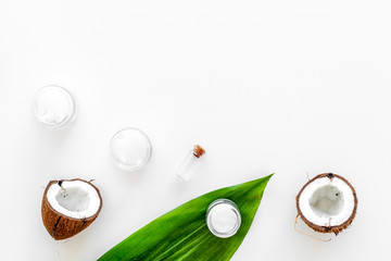 Coconut oil cosmetics for skin and hair care. Oil in small bottle, cream jar, halfs of coconut with shelf, palm leaves on white background top view copy space