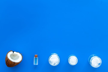 Cosmetics based on coconut oil. Oil in small bottle, cream, coconut pulp, half of coconut with shelf on blue background top view copy space pattern