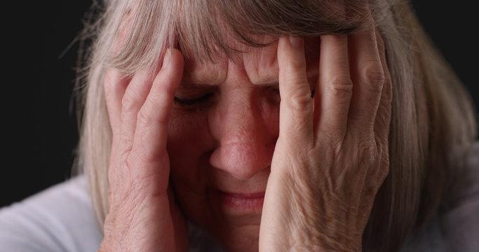Tight shot of elderly woman with migraine headache rubbing head on gray backdrop
