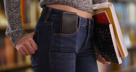 Tight shot of mid section of girl with mobile phone in pocket while at library