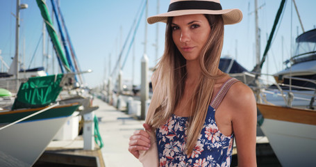 Stylish attractive woman in her 20s wearing fedora and romper standing on marina