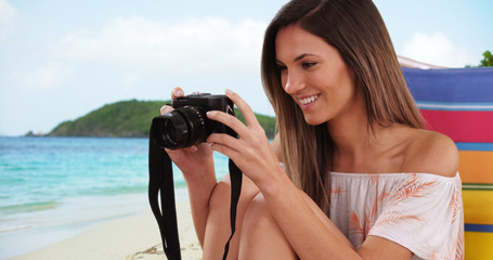 Pretty girl taking photo with camera while sitting at beach on tropical vacation