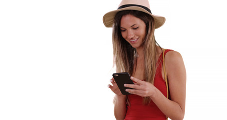 Happy millennial woman in hat and tank top using phone app on white copy space