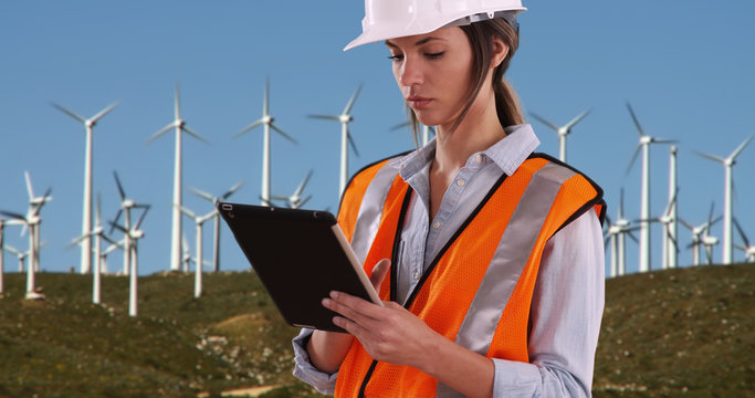 Woman in orange vest and hardhat working on tablet by wind turbines outdoors