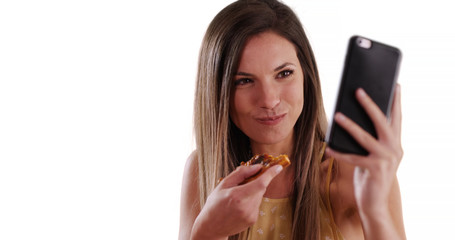 Close-up of girl taking selfie with phone while eating pizza on white background