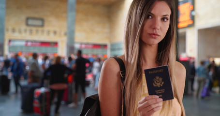 Portrait of woman traveler showing US Passport to camera in train station lobby