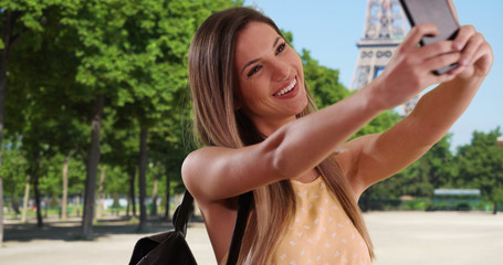 White woman in her 20s taking snap of herself with phone by Eiffel Tower