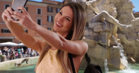 Happy millennial girl taking selfie with smartphone by Fiumi Fountain in Rome