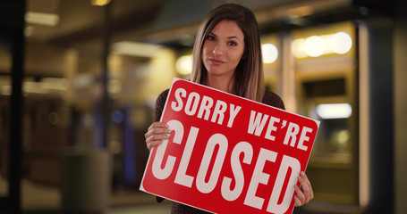 Female small business owner standing with Closed sign outside store at night