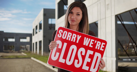 Woman holding Closed sign outside some abandoned buildings