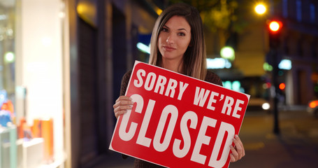 Young Female business owner looking at camera with Closed sign outside store