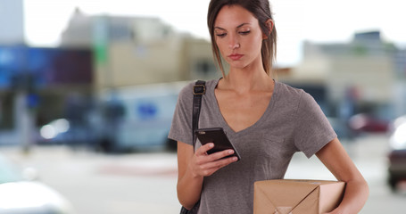Millennial female using smartphone app to track package outside in city setting
