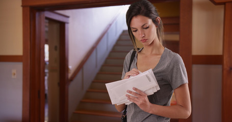 White millennial female checking stack of letters standing inside her house