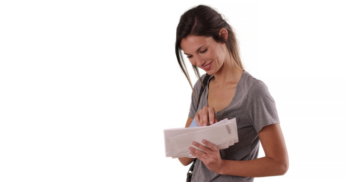Young Caucasian woman looking through mail she received on white copy space