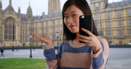 Close up of cute tourist taking selfie with smartphone by Westminster palace