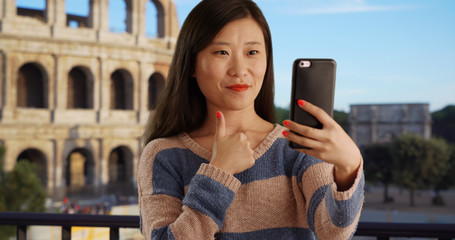 Close up of cute woman taking selfie using smartphone camera by Roman Colosseum