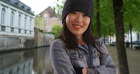 Cold millennial female wearing beanie and mittens in Bruges Belgium