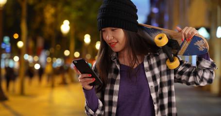 Happy millennial skater taking selfie with skateboard in Champs Elysees