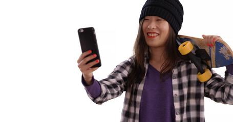 Lovely millennial skater using technology to take selfie for copy space