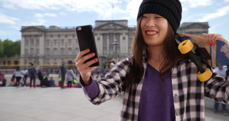 Lovely millennial skater using technology to take selfie in London UK