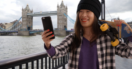 Lovely millennial skater using smart phone for selfie in London UK