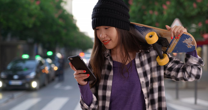 Happy millennial skater taking selfie with skateboard on city street