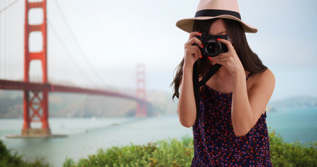Close up of young tourist using camera by Golden Gate bridge in San Francisco
