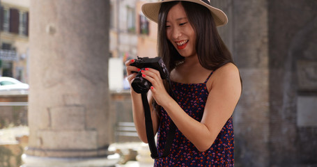 Closeup of Asian millennial photographer taking pictures in Rome Italy