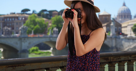 Closeup of Asian millennial photographer taking pictures by the Vatican in Rome
