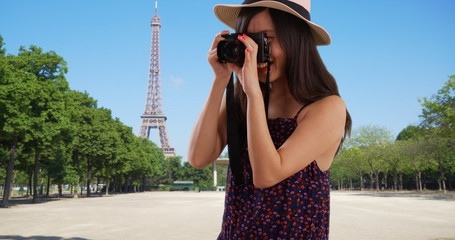 Closeup of Asian millennial photographer taking photos by Eiffel Tower in Paris